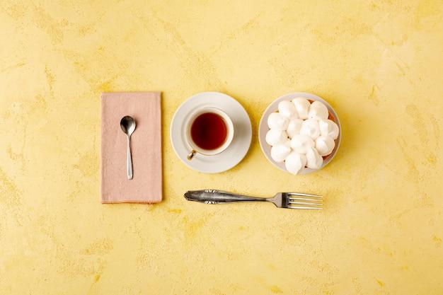 Plat lag assortiment met thee en cake op gele achtergrond Gratis Foto