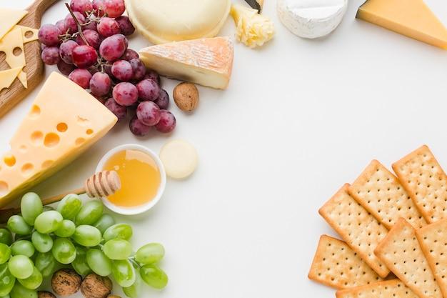 Plat lag assortiment van gastronomische kaas en druiven met crackers Gratis Foto