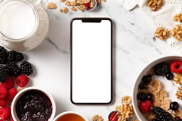 Plat lag assortiment van gezonde komgranen met lege scherm smartphone Gratis Foto