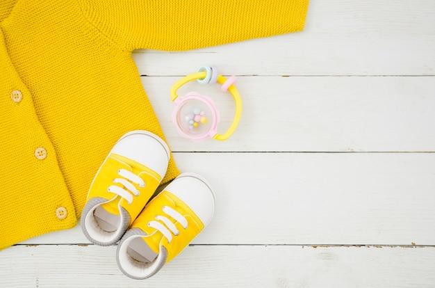 Plat lag babykleding met houten achtergrond Gratis Foto