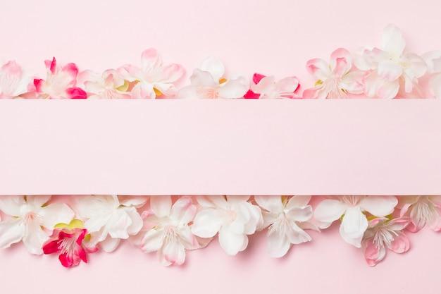 Plat lag bloemen op roze achtergrond met blanco papier Gratis Foto