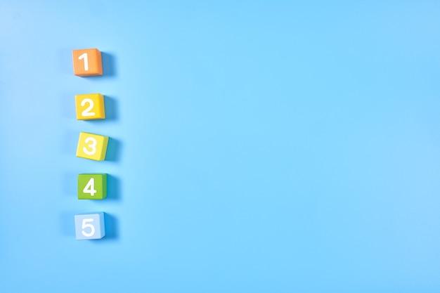 Plat lag bovenaanzicht van helder gekleurde cijferblokjes met getallen Premium Foto