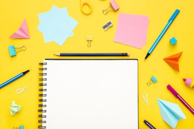 Plat lag briefpapier arrangement op gele achtergrond met lege notebook Gratis Foto