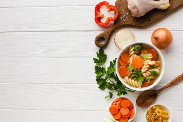 Plat lag broccoli wortelen en fusilli in kom met kip drumstick op snijplank met kopie ruimte Gratis Foto