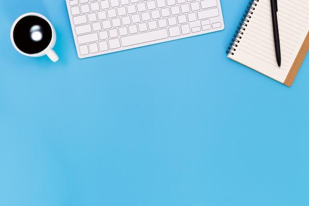 Plat lag bureau tafel van moderne werkplek met laptop op blauwe tafel, bovenaanzicht laptop achtergrond en kopie ruimte op zwarte achtergrond, blauwe bureau kantoor met laptop, Premium Foto