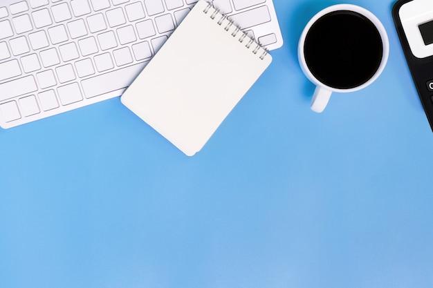Plat lag bureau tafel van moderne werkplek met laptop op blauwe tafel, bovenaanzicht laptop Premium Foto