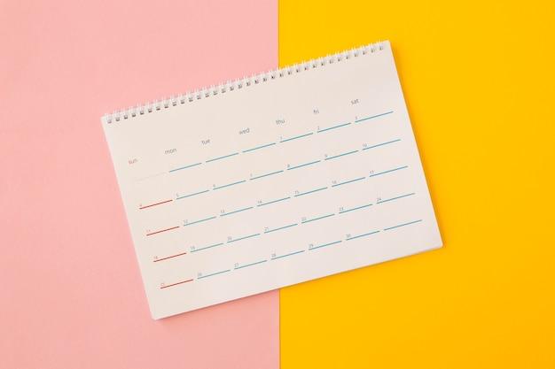 Plat lag bureaukalender op gele en roze achtergrond Premium Foto