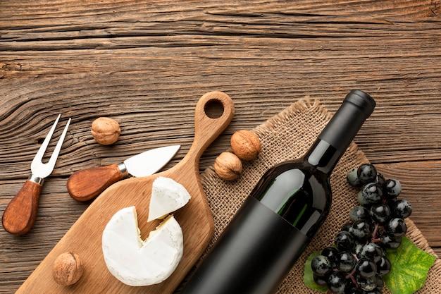 Plat lag camembert op houten snijplank druiven en walnoten met gebruiksvoorwerpen Gratis Foto