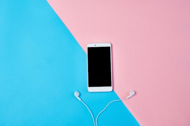 Plat lag compositie met smartphone, koptelefoon op een blauwe en roze achtergrond. Premium Foto