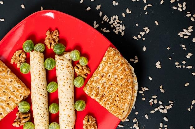 Plat lag crêpes arrangement op een rode plaat Gratis Foto