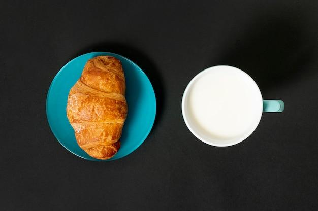 Plat lag croissant en kopje melk op effen achtergrond Gratis Foto