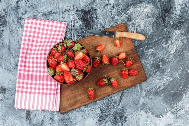 Plat lag een kom aardbeien en een mes op een houten snijplank met rood geruit tafelkleed op donkerblauw marmeren oppervlak. horizontaal Gratis Foto