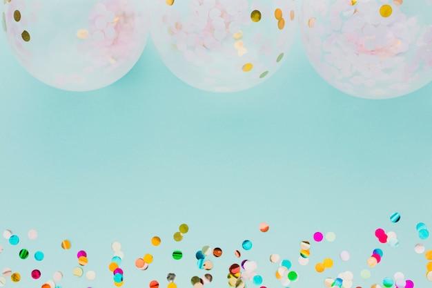 Plat lag feestdecoratie met ballonnen en blauwe achtergrond Gratis Foto