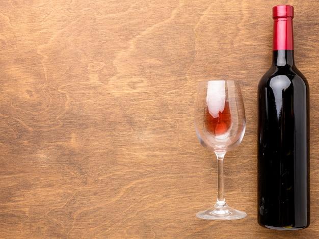 Plat lag fles wijn en glas met kopie-ruimte Gratis Foto