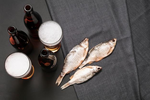 Plat lag flessen en glazen bier met vis Gratis Foto