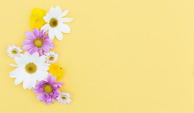 Plat lag floral frame met gele achtergrond Gratis Foto
