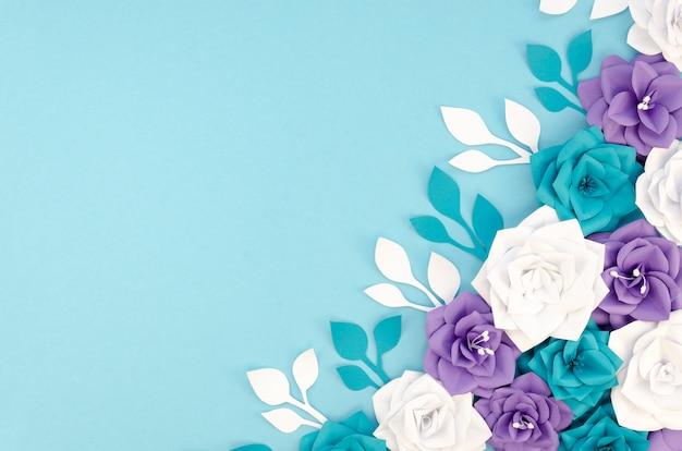 Plat lag frame met bloemen en blauwe achtergrond Gratis Foto