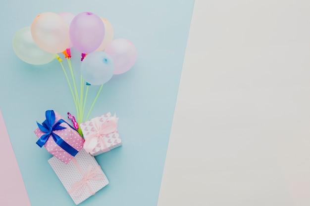 Plat lag frame met kleurrijke ballonnen en geschenken Gratis Foto
