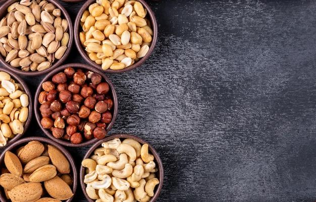 Plat lag geassorteerde noten en gedroogde vruchten in verschillende mini kommen met pecannoten, pistachenoten, amandel, pinda Gratis Foto