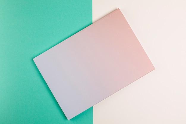Plat lag gesloten boek met kleurrijke achtergrond Gratis Foto