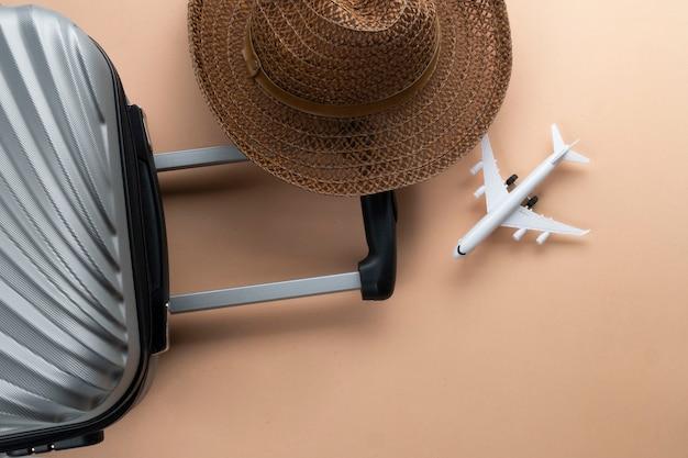Plat lag grijze koffer met bruine hoed en mini-vliegtuig Premium Foto
