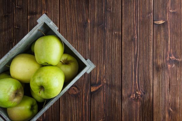 Plat lag groene appels in houten kist op houten achtergrond. horizontale vrije ruimte voor uw tekst Gratis Foto