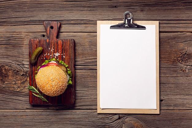 Plat lag hamburger met mock-up klembord Gratis Foto