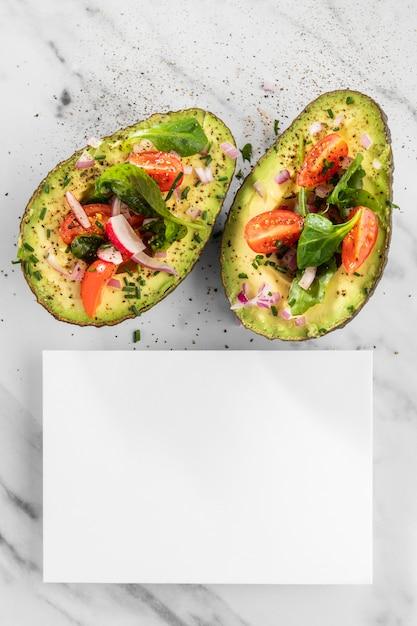 Plat lag heerlijke gezonde salade in avocado-samenstelling met een witte kaart Gratis Foto