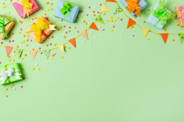 Plat lag kleurrijke geschenken op tafel met groene achtergrond Gratis Foto