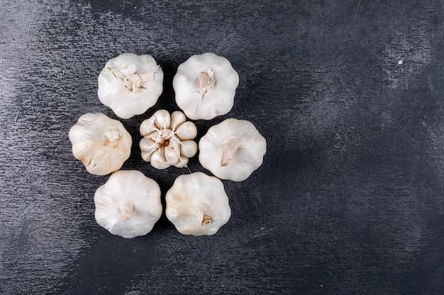 Plat lag knoflook vorm bloemvorm op donkere tafel Gratis Foto