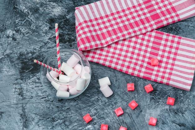 Plat lag marshmallows en suikerriet in pot met snoepjes en rood pastel tafelkleed op donkerblauw marmeren oppervlak. horizontaal Gratis Foto