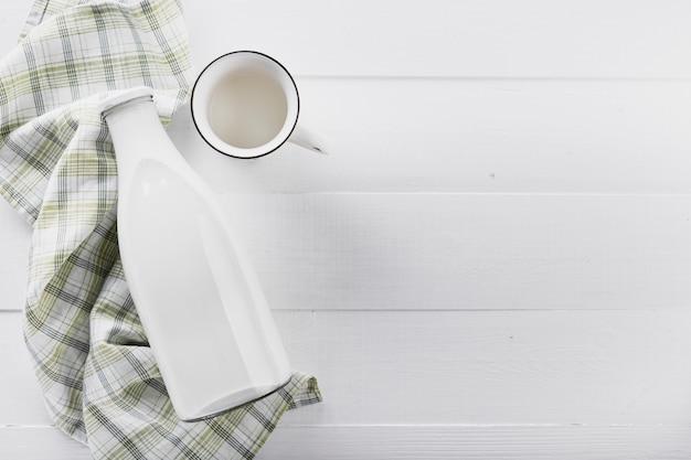 Plat lag melk fles met cup op tafel Gratis Foto