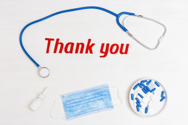 Plat lag met medische stethoscoop, pillen, wegwerpmasker en tekst bedankt Premium Foto