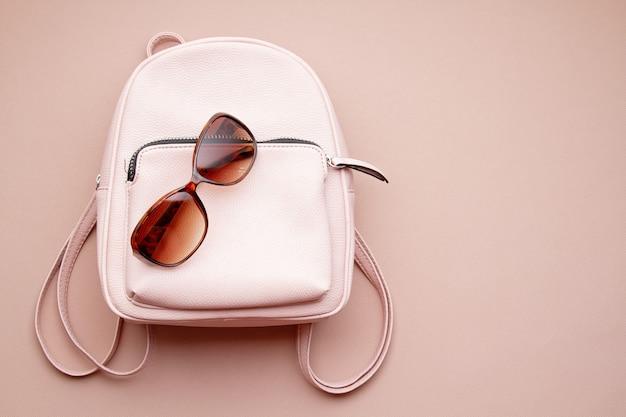 Plat lag met roze vrouw accessoires met rugzak en vrouw hand met de zonnebril. zomer modetrends, winkelen idee Premium Foto