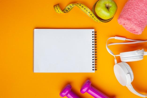 Plat lag notebook en appel op gele achtergrond Gratis Foto