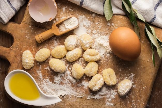 Plat lag ongekookte aardappel gnocchi op snijplank met eieren Gratis Foto