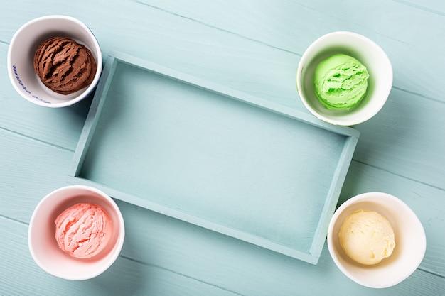 Plat lag, overhead shoot van zelfgemaakt assortiment ijs op lichtblauwe houten ondergrond. gezond zomervoedselconcept. bovenaanzicht, kopieer ruimte Premium Foto