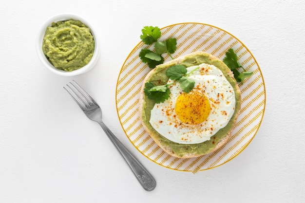 Plat lag pitabroodje met avocado-spread en gebakken ei op plaat met vork Gratis Foto