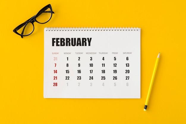 Plat lag planner kalender op gele achtergrond Gratis Foto