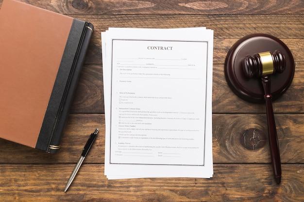 Plat lag rechter hamer en boek met contract Gratis Foto