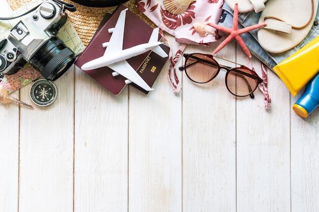 Plat lag reiziger accessoires op witte houten tafel. bovenaanzicht reizen of vakantie concept. Premium Foto