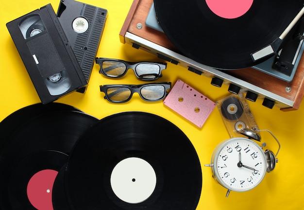 Plat lag retro stijl attributen, 80s media. vinyl speler, videocassettes, audiocassettes, platen, 3d-bril, vintage wekker, oude boeken op gele achtergrond. bovenaanzicht Premium Foto