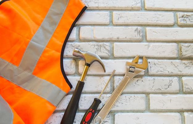 Plat lag samenstelling met beschermende constructie vest en werk hulpmiddel op bakstenen muur achtergrond Premium Foto