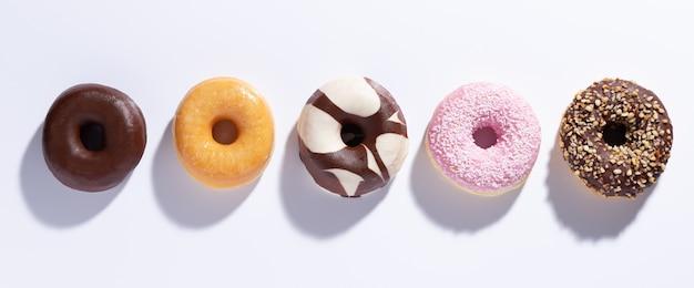 Plat lag samenstelling met gemengde donuts op witte achtergrond. Premium Foto