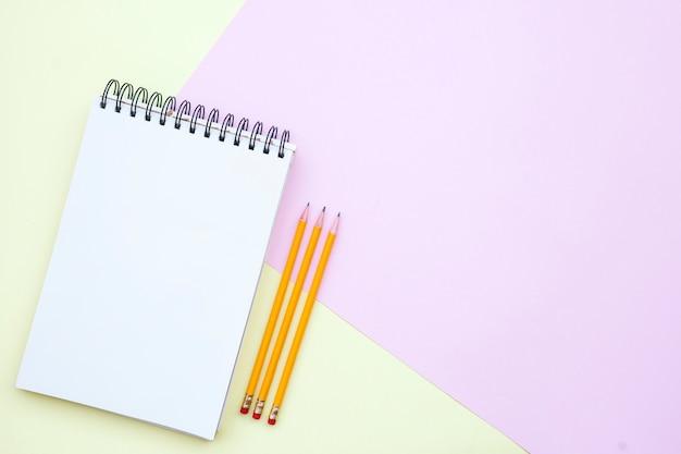 Plat lag samenstelling met lege notebook met potloden op roze en gele achtergrond Gratis Foto