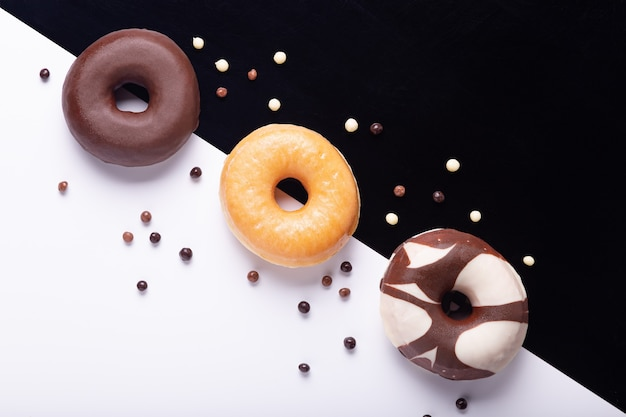 Plat lag samenstelling van drie donuts op zwarte en witte achtergrond. Premium Foto