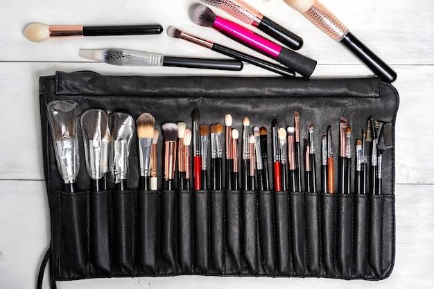 Plat lag set van zwarte make-up kwasten in een zwart lederen etui. Premium Foto