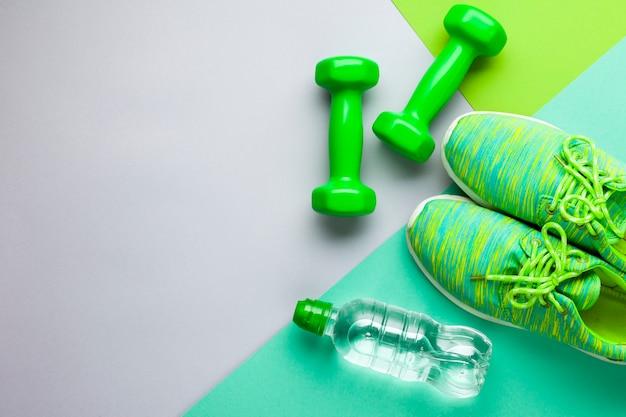 Plat lag sportattributen met waterfles en schoenen Gratis Foto