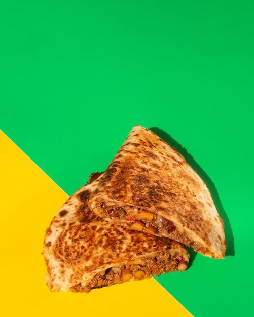 Plat lag tortilla krokant brood op groene en gele achtergrond Gratis Foto