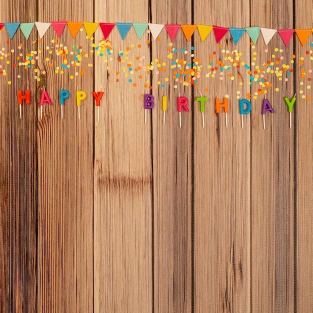 Plat lag verjaardag ornamenten op houten achtergrond Gratis Foto